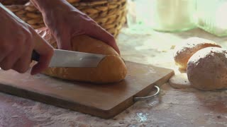 Slicing fresh  wheat bread on the table