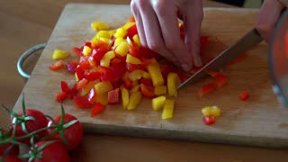 Slicing red and yellow pepper on chopping board, super slow motion, shot at 240fps