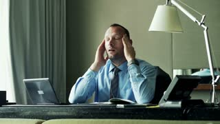 Tired businessman having headache sitting at office desk