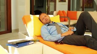 tired businessman sleeping on sunbed