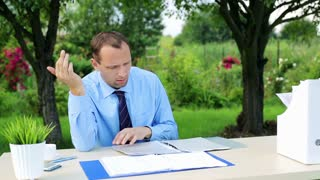 tired, overwhelmed businessman working with documents in the garden