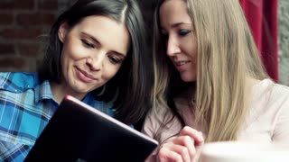 Two beautiful girlfriends with tablet talking and smiling in cafe