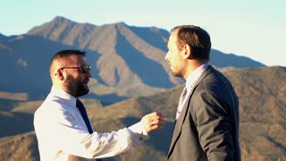 Two businessmen fighting in the mountains, super slow motion