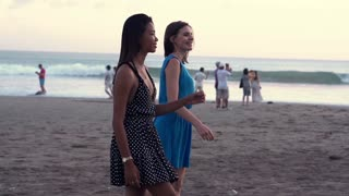 Two female friends chatting during walking on the beach, super slow motion, shot at 240fps
