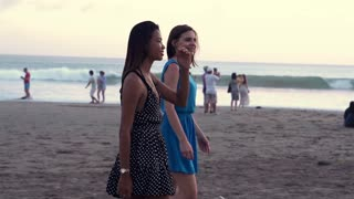 Two female friends chatting during walking on the beach