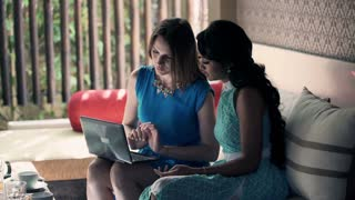Two female girlfriends talking over laptop computer on sofa at home