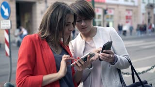 Two girlfriends talking and using smartphone standing in the city, 4K