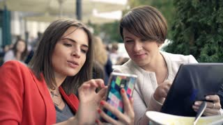 Two girlfriends using smartphone and tablet and talking in cafe in the city, 4K