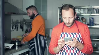 Two men in aprons cooking and checking smartphone in the kitchen at home