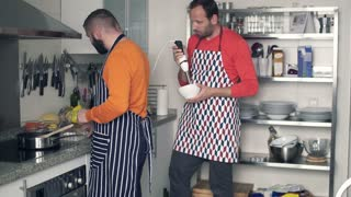 Two men in aprons cooking in the kitchen at home