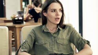 Unhappy, impatient woman waiting for someone in cafe