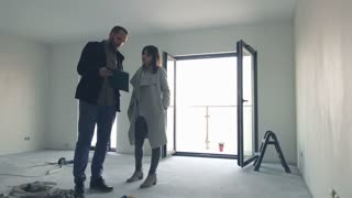 Unhappy real estate agent talking to female client at new home