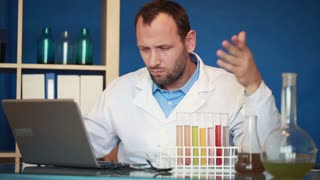 Unhappy young scientist with test tube in laboratory