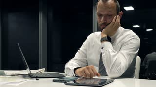 Bored businessman sitting by desk in office by night