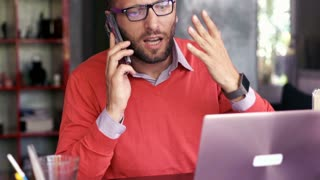 Angry businessman with laptop talking on cellphone at home