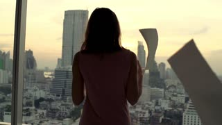 Angry businesswoman throwing documents by window in office during sunset, super slow motion