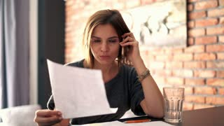 Angry businesswoman with documents talking on cellphone at home