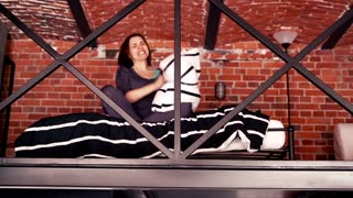 Angry woman hitting pillow in mezzanine bedroom