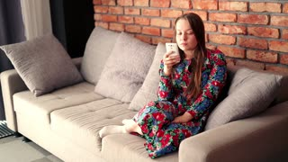 Angry woman talking on cellphone while sitting on sofa at home