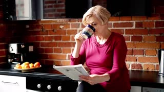 Beautiful, mature woman reading newspapers in the kitchen