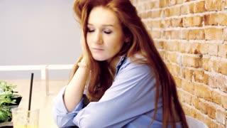 Beautiful, sad woman sitting in a cafe