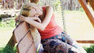 Beautiful, sad woman sitting on the swing in the garden