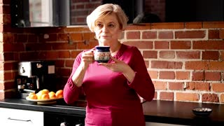 Beautiful, senior woman drinking tea and relaxing in the kitchen