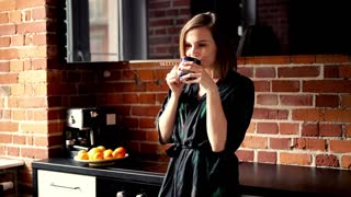 Beautiful woman drinking coffee in the kitchen