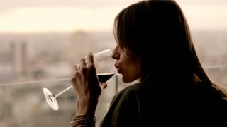 Beautiful woman drinking red wine while sitting in rooft bar in the city