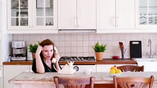 Beautiful woman talking by old telephone in the kitchen