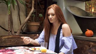 Beautiful woman with red hair gets stomach ache during meal in vegetarian cafe