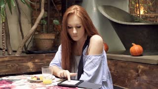 Beautiful woman with red hair reading something on e-book sitting in vegetarian cafe