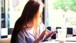 Beautiful woman with red hair using smartphone in cafe