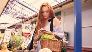 Beautiful woman with smartphone choosing delicious vegetables at local farmers market