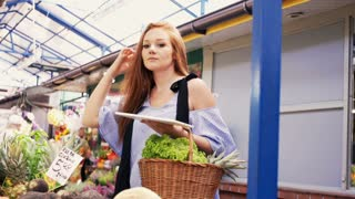 Beautiful woman with tablet checking vegetables at local farmers market