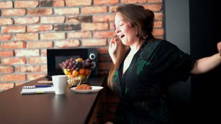 Beautiful woman yawning by table in the kitchen