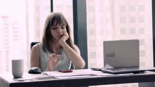 Bored businesswoman with laptop and smartphone sitting in the office