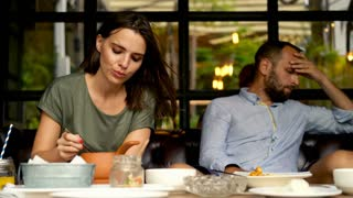 Bored, resentful couple sitting by the table during breakfast