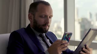 Businessman comparing data on tablet computer and smartphone on armchair by the window in the office