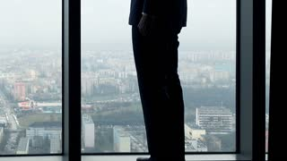 businessman silhouette drinking coffee while standing by window in