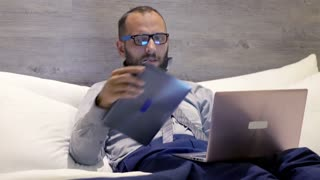 Businessman working with tablet and laptop on bed