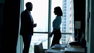 Businesspeople making deal and shaking hands by window in office, 4K