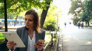 Businesswoman comparing data on tablet and smartphone on the bench in the city