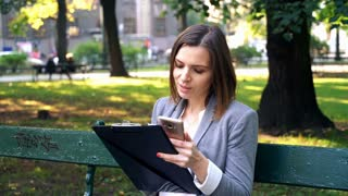 Businesswoman comparing documents with smartphone on the bench in the city