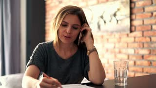 Businesswoman making notes while talking cellphone at home
