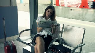 Businesswoman reading newspaper and looking for job at the railway station