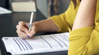 Businesswoman signing documents in the office, focus on hands