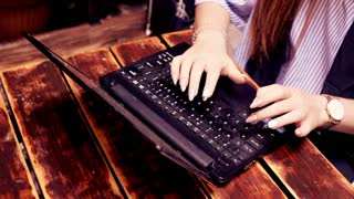 Close up of female hands typing on laptop on wooden table