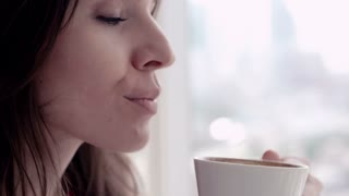 Close up of happy, pretty woman drinking coffee