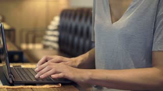 Closeup of female hands typing on modern laptop at cafe